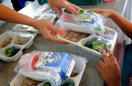 (AP Photo/Matt York,File). FILE - In this July 22, 2104 file photo Children receive a free lunch at the Phoenix Day @ Central Park Youth Program in downtown Phoenix. Signs of entrenched childhood poverty, hunger and disparities in education have shifte...
