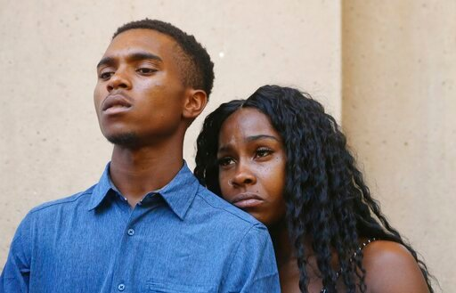 (AP Photo/Ross D. Franklin). Dravon Ames, left, and Iesha Harper pause as they listen to a question during a news conference at Phoenix City Hall, Monday, June 17, 2019, in Phoenix. Ames and his pregnant fiancée, Harper, who had guns aimed at them by P...