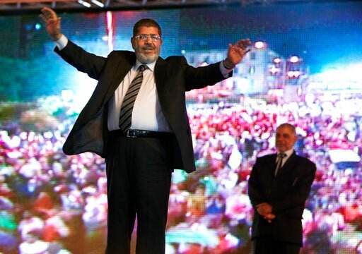(AP Photo/Fredrik Persson, File). FILE - In this May 20, 2012 file photo, then Muslim Brotherhood's presidential candidate Mohammed Morsi holds a rally in Cairo, Egypt. On Monday June 17, 2019, Egypt's state TV says the country's ousted President Moham...