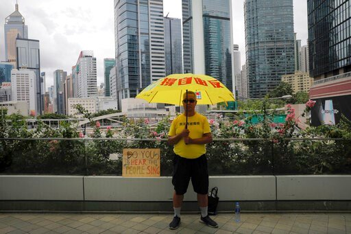 (AP Photo/Vincent Yu). A man holds an umbrella outside the Legislative Council following last weekend's massive protest against the unpopular extradition bill in Hong Kong, Tuesday, June 18, 2019. Hong Kong's government headquarters reopened Tuesday as...
