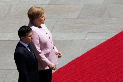 (AP Photo/Markus Schreiber). German Chancellor Angela Merkel, right, and Ukrainian President Volodymyr Zelenskiy, left, listen to the national anthems during the welcoming ceremony, prior to a meeting at the chancellery in Berlin, Germany, Tuesday, Jun...