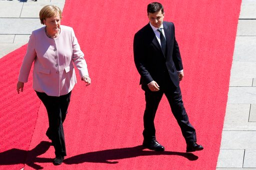 (AP Photo/Markus Schreiber). German Chancellor Angela Merkel, left, and Ukrainian President Volodymyr Zelenskiy, right, review the honour guards during the welcoming ceremony prior to a meeting at the chancellery in Berlin, Germany, Tuesday, June 18, 2...
