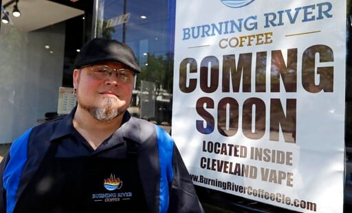 """(AP Photo/Tony Dejak). Johnny Rowan stands outside Burning River Coffee, Friday, June 14, 2019, in Lakewood, Ohio. Rowan's is one of 90 active businesses registered with the state that have """"burning river"""" in their names, inspired by the Cuyahoga River..."""