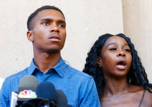 (AP Photo/Ross D. Franklin). Iesha Harper, right, answers a question during a news conference as she is joined by her fiancee Dravon Ames, left, at Phoenix City Hall, Monday, June 17, 2019, in Phoenix. Ames and his pregnant fiancée, Harper, who had gun...