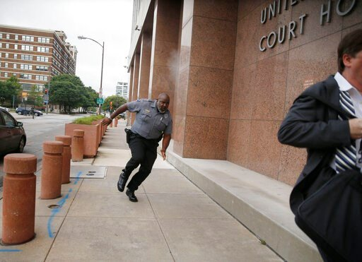 (Tom Fox/The Dallas Morning News via AP). A security guard and a civilian run for cover as bullets ricochet off the building as a shooter (far background left) fires towards them on Monday, June 17, 2019 at the Earle Cabell federal courthouse in Dallas...