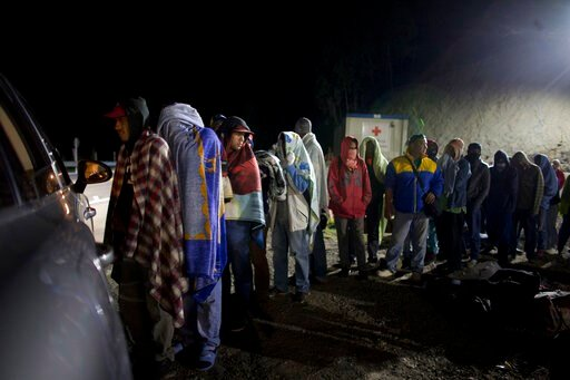 (AP Photo/Ariana Cubillos). FILE - In this Aug. 31, 2018 file photo, Venezuelan migrants line up for free bread and coffee, donated by a Colombian family from their car, at a gas station in Pamplona, Colombia. A record 71 million people have been displ...