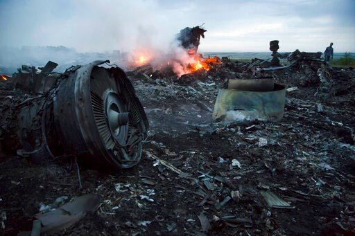 (AP Photo/Dmitry Lovetsky, File). FILE - In this Thursday, July 17, 2014 file photo, a man walks amongst the debris at the crash site of a passenger plane near the village of Hrabove, Ukraine. An international team of investigators building a criminal ...