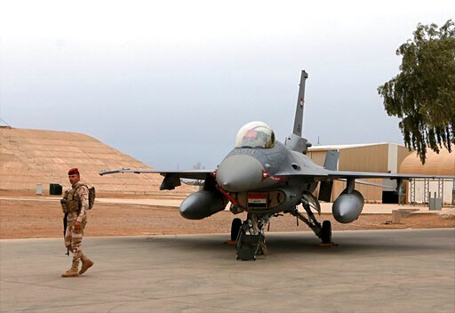 (AP Photo/Khalid Mohammed, File). FILE - in this Tuesday, Feb. 13, 2018 file photo, an Iraqi army soldier stand guard near a U.S.- made Iraqi Air Force F-16 fighter jet at the Balad Air Base, Iraq. Militants fired early Saturday, June 15, 2019,  three ...