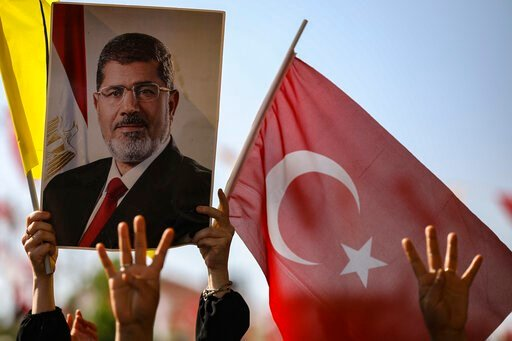 (AP Photo/Emrah Gurel). Supporters join Turkish President Recep Tayyip Erdogan, who attends funeral prayers in absentia for ousted former Egyptian President Mohammed Morsi, in poster, at Fatih Mosque in Istanbul, Tuesday, June 18, 2019. Funeral prayers...