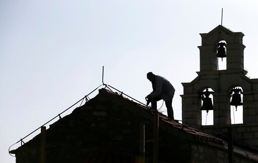 "(AP Photo/Darko Vojinovic, File). In this Wednesday, March 15, 2017 file photo, a worker fixes roof on Holy Sunday church in the 'Tsar's Village' complex near Sveti Stefan peninsula in Montenegro. A Serb official has branded Montenegro a ""criminal"" sta..."