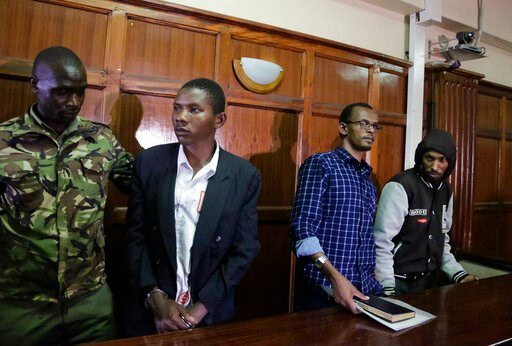 (AP Photo/Khalil Senosi). From left to right, defendants Rashid Charles Mberesero, Hassan Aden Hassan and Mohamed Abdi Abikar, are led from the dock by a police officer, left, after their verdict at a court in Nairobi, Kenya Wednesday, June 19, 2019. T...