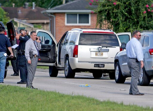 (Michael DeMocker/The Times-Picayune via AP). The Jefferson Parish Sheriff's Office investigates the scene in Metarie Tuesday, June 18, 2019 after two men were shot to death inside a Cadillac Escalade near the intersection of West Metairie Avenue and N...