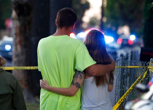 (AP Photo/Rich Pedroncelli). A man and woman watch as law enforcement officers surround a home where a gunman has taken refuge after shooting a Sacramento police officer, Wednesday, June 19, 2019, in Sacramento, Calif.