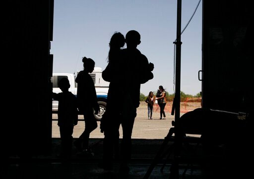 (AP Photo/Cedar Attanasio, File). FILE - In this Wednesday, May 22, 2019 file photo migrants mainly from Central America guide their children through the entrance of a World War II-era bomber hanger in Deming, N.M. A panel of appeals court judges in Ca...