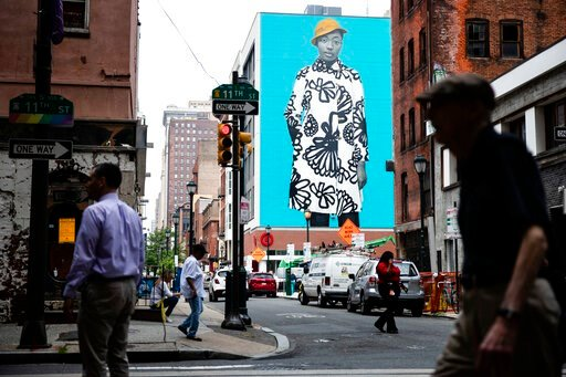 (AP Photo/Matt Rourke). In this Tuesday, June 18, 2019 photo, pedestrians walk near a Mural Arts Philadelphia mural of Najee Spencer-Young by artist Amy Sherald by in Philadelphia. Sherald is the artist who painted the official portrait of Michelle Oba...