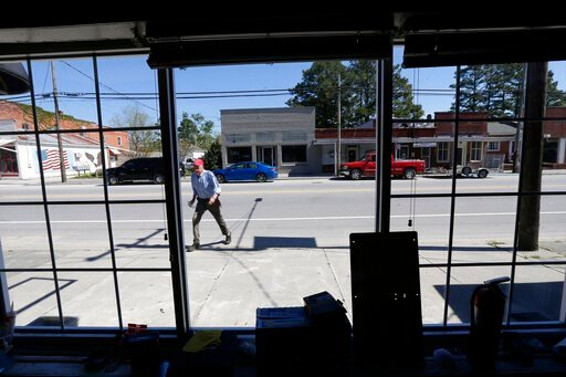 (AP Photo/Gerry Broome). In this photo taken Wednesday, April 17, 2019 town manager Glenn Spivey crosses Jones Street in Trenton, N.C. Eight months after Hurricane Florence inundated North Carolina, communities such as Trenton illustrate the slow and u...