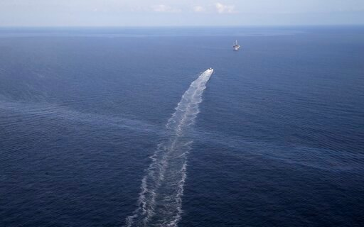 (AP Photo/Gerald Herbert, File). FILE- In this March 31, 2015 aerial photo, the wake of a supply vessel heading towards a working platform crosses over an oil sheen drifting from the site of the former Taylor Energy oil rig in the Gulf of Mexico, off t...