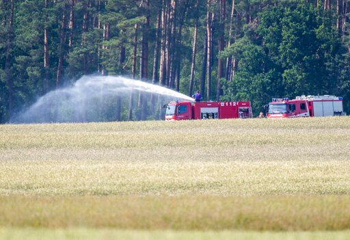 (Jens Buettner/dpa via AP). Firefighters work in Nossentiner Huette, eastern Germany on Monday, June 24, 2019 where two German Eurofighter military planes crashed earlier today.