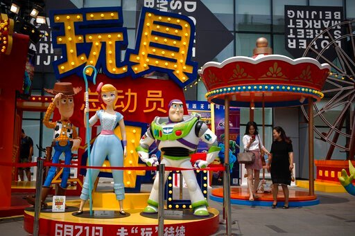 """(AP Photo/Andy Wong). A woman browses her photo after taking with her friend near the American latest animated film """"Toy Story 4"""" promotion decoration on display at the capital city's popular shopping mall in Beijing, Tuesday, June 25, 2019. China says..."""