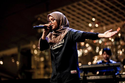 """(AP Photo/Wani Hamid). In this June 29, 2019, photo, Malaysian female rapper Bunga performs at """"Pesta Raya"""" festival in Singapore. Bunga, whose real name is Noor Ayu Fatini Mohd Bakhari, is one of the only known rappers who wears a hijab and baju kurun..."""