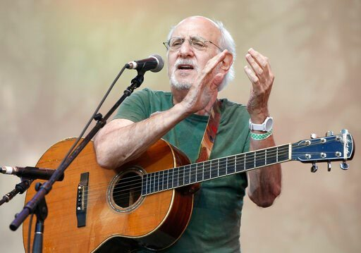 """(AP Photo/Kathy Willens, File). FILE - In this July 20, 2014, file photo, singer-songwriter Peter Yarrow, of the 1960's era musical trio """"Peter Paul and Mary,"""" claps and encourages the audience to sing along during a memorial tribute concert for folk i..."""