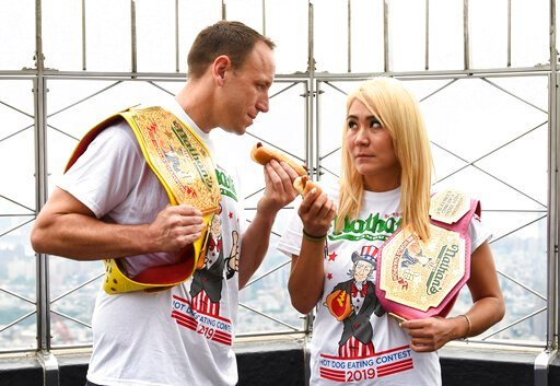 (Photo by Evan Agostini/Invision/AP). Eleven-time and defending men's champion Joey Chestnut, left, and defending women's champion Miki Sudo pose together during Nathan's Famous international Fourth of July hot dog eating contest weigh-in at the Empire...