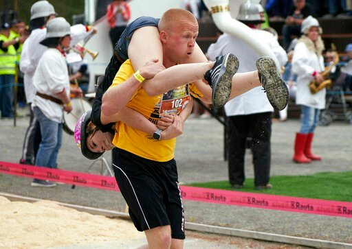 (AP Photo/David Keyton). People take part in the wife carrying race, a 278-yard obstacle course, during the 24th world championships in Sonkajarvi, Finland, Saturday, July 6, 2019. Despite the event's name couples don't have to be married, and organize...