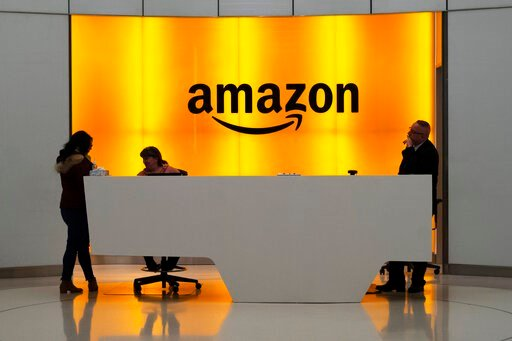 """(AP Photo/Mark Lennihan, File). FILE - In this Feb. 14, 2019, file photo people stand in the lobby for Amazon offices in New York. Amazon and Microsoft are battling for a $10 billion opportunity to build the U.S. military its first """"war cloud."""""""