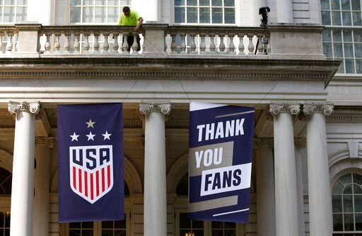 (AP Photo/Kathy Willens). A worker hangs signs at City Hall one day ahead of a ticker-tape parade for the U.S. Women's World Cup winning team, Tuesday, July 9, 2019, in New York.