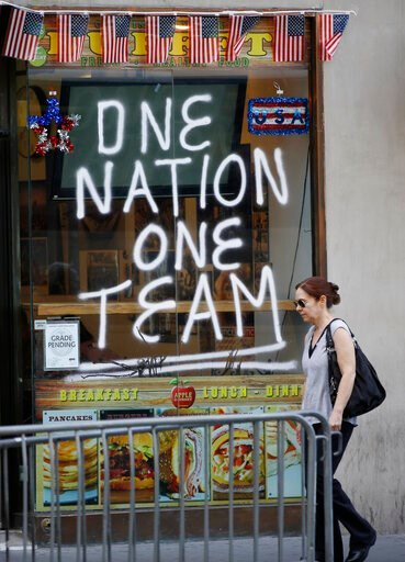 (AP Photo/Kathy Willens). A woman walks past a sign painted on a delicatessen across the street from City Hall one day ahead of a ticker-tape parade for the U.S. Women's soccer team, four-time World Cup winners, Tuesday, July 9, 2019, in New York.