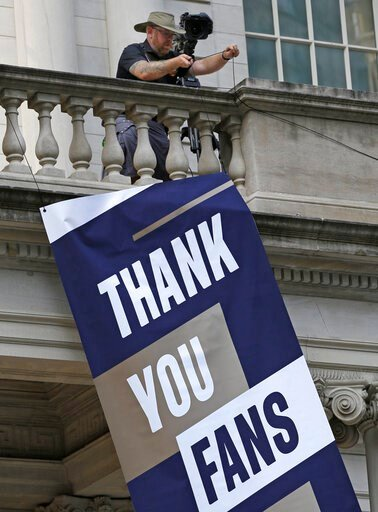 (AP Photo/Kathy Willens). A worker hangs a banner from the balcony at New York City Hall, one day ahead of a ticker-tape parade and ceremony planned for the four-time World Cup winning U.S. Women's soccer team, Tuesday, July 9, 2019, in New York.