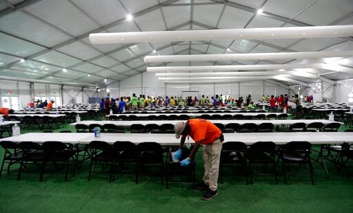 (AP Photo/Eric Gay). In this July 9, 2019, photo, a staff member cleans in a dinning hall at the U.S. government's newest holding center for migrant children in Carrizo Springs, Texas. The government said the holding center will give it much-needed cap...