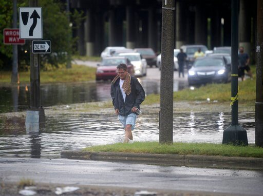 (Max Becherer/The Advocate via AP). A man walks through standing water at the intersection at Franklin Ave. and 610 in New Orleans after a severe thunderstorm caused street flooding Wednesday, July 10, 2019.