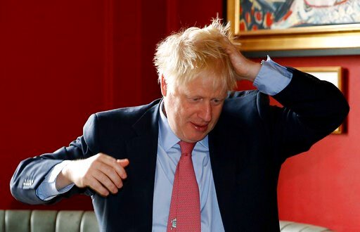 (Henry Nicholls/Pool Photo via AP). Conservative Party leadership candidate Boris Johnson gestures during a visit to Wetherspoons Metropolitan Bar in London, Wednesday July 10, 2019.