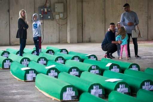 (AP Photo/Darko Bandic). Relatives inspect coffins prepared for burial, in Potocari near Srebrenica, Bosnia, Wednesday, July 10, 2019. The remains of 33 victims of Srebrenica massacre will be buried on July 11, 2019, 24 years after Serb troops overran ...