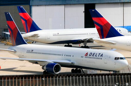 (AP Photo/Mark Lennihan). FILE - In this April 20, 2010 file photo, Delta Air Lines jets are parked at John F. Kennedy International Airport, in New York. U.S. Customs and Border Protection will issue a new policy directive under a settlement agreement...