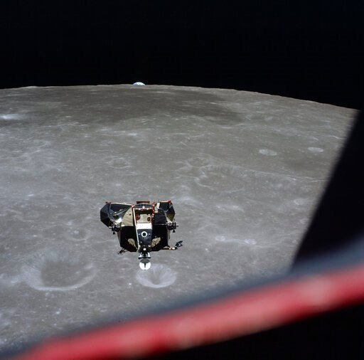 (Michael Collins/NASA via AP). This July 21, 1969 photo made available by NASA shows the Lunar Module approaching the Command Module with the Earth visible behind the moon. The shutter speeds on the astronauts' cameras were too fast to capture the fain...
