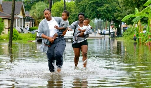 (AP Photo/Matthew Hinton). Jalana Furlough carries her son Drew Furlough as Terrian Jones carries Chance Furlough on Belfast Street near Eagle Street in New Orleans after flooding from a tropical wave system in the Gulf Mexico that dumped lots of rain ...
