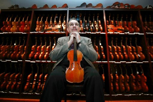 (Suchat Pederson/The News Journal via AP). In this 2009 photo, musician David Bromberg poses with some of his 263 historic American violins in Wilmington, Del. Bromberg, known for collaborating with Bob Dylan and the Beatle's George Harrison, was set t...