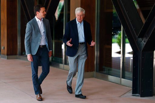 (AP Photo/David Zalubowski, File). FILE - In this June 29, 2019, file photo, Charles Koch, chief executive officer of Koch Industries, right, talks with Brian Hooks, a network leader for Koch Industries, at The Broadmoor Resort in Colorado Springs, Col...