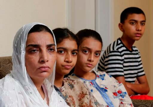 (AP Photo/Michael Wyke). In this Wednesday July 10, 2019 photo, family members of Santa Fe High School shooting victim Sabika Aziz Sheikh, 17, pose in their home during an interview in Houston., They are, from left, Farah Naz, mother; sisters Sonia Azi...