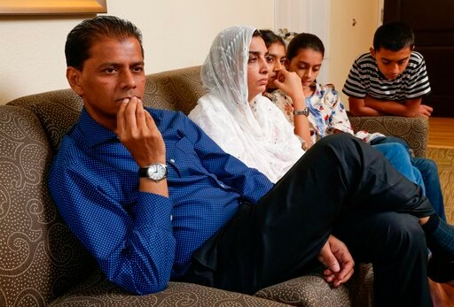 (AP Photo/Michael Wyke). In this Wednesday July 10, 2019 photo, family members of Santa Fe High School shooting victim Sabika Aziz Sheikh, 17, pose in their home during an interview in Houston., They are, from left, Abdul Aziz, father; Farah Naz, mothe...