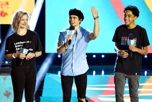 (Photo by Chris Pizzello/Invision/AP, File). FILE - In this April 25, 2019, file photo, Cameron Boyce, center, speaks at WE Day California, as Macy Lillard, left, and Jazzy Satten look on at The Forum in Inglewood, Calif. Actor Cameron Boyce, known for...