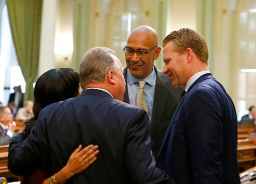 (AP Photo/Rich Pedroncelli). Democratic state lawmakers, from left, Assemblywoman Autumn Burke, of Inglewood, State Sen. Bill Dodd, of Napa, Assemblyman Chris Holden, of Pasadena, and Republican Assemblyman Chad Mayes, of Yucca Valley, right, celebrate...