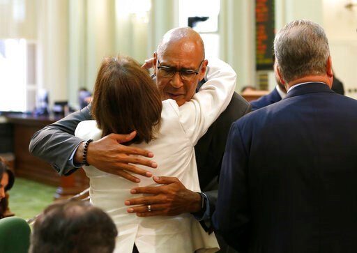 (AP Photo/Rich Pedroncelli). Assemblyman Chris Holden, D-Pasadena, center, is hugged by Assemblywoman Cecilia Aguiar-Curry, D-Winters, after the wildfire measure he co-authored, with Assembly members Autumn Burke, D-Inglewood and Chad Mayes, R-Yucca Va...