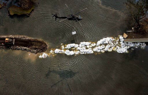 (AP Photo/David J. Phillip, File). FILE - In this Sept. 5, 2005, file photo, a military helicopter drops a sandbag as work continues to repair the 17th Street canal levee in New Orleans, in the aftermath of Hurricane Katrina. After Hurricane Katrina's ...