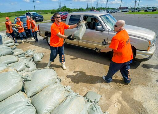 (AP Photo/Matthew Hinton). St. Bernard Parish Sheriff's Office inmate workers move free sandbags for residents in Chalmette, La., Thursday, July 11, 2019 ahead of ahead of Tropical Storm Barry from the Gulf of Mexico.