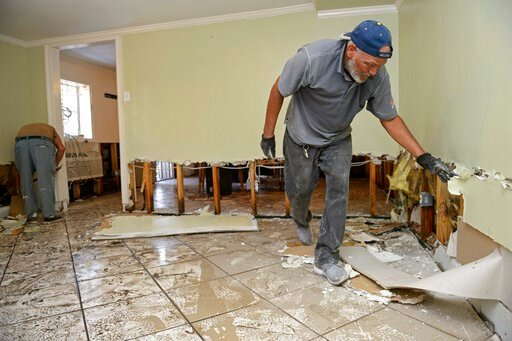 (Max Becherer/The Advocate via AP). Joe Miles, right, and Rey Varea, left, cut out drywall to prevent mold the day after severe weather flooded the home in the Broadmoor neighborhood in New Orleans, Thursday, July 11, 2019.