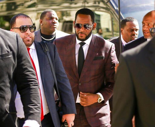 (AP Photo/Amr Alfiky, File). FILE - In this June 26, 2019, file photo, R&B singer R. Kelly, center, arrives at the Leighton Criminal Court building for an arraignment on sex-related felonies in Chicago. Kelly, who was arrested in Chicago on July 11...