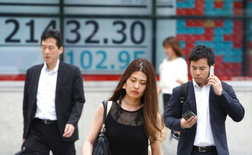 (AP Photo/Koji Sasahara). People walk by an electronic stock board of a securities firm in Tokyo, Wednesday, July 17, 2019. Asian stocks were mixed Wednesday as Wall Street ended a five-day winning streak after the first big round of corporate earnings...